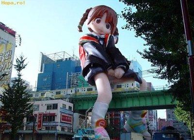 boneca japonesa gigante sentada sobre ponte de trem, suspensa sobre a rua