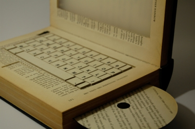 notebook escavado dentro de um livro aberto