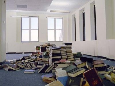 sala vazia com pilhas desarrumadas de livros