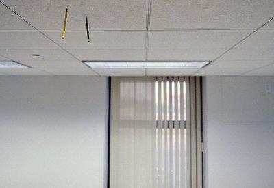 sala vazia com 2 lapis fincados no teto