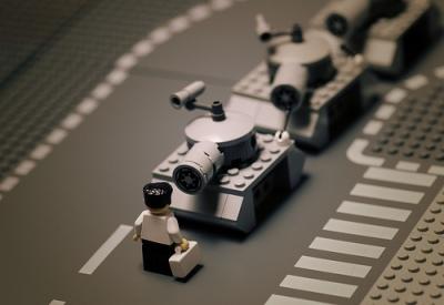 homem em frente a tanques, feito de lego