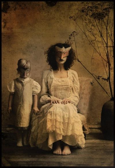 Mulher e criança usando mascaras de bicho, sentadas em pose antiga