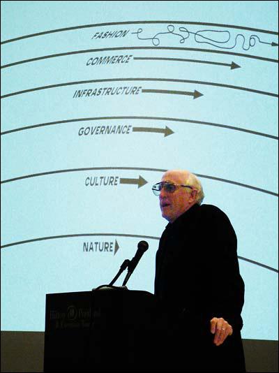 homem falando em frente a telao com linhas curvas de órbitas