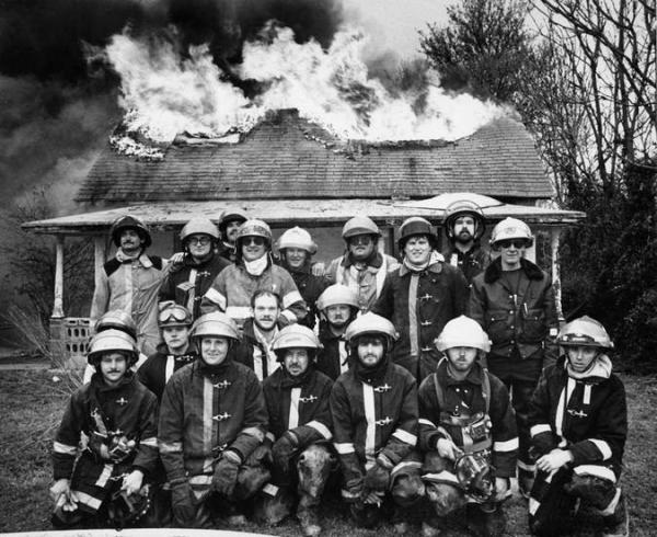 bombeiros tirando foto em frente a casa pegando fogo