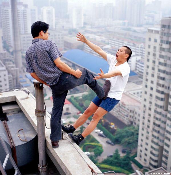homem sendo chutado e caindo na beirada de um prédio