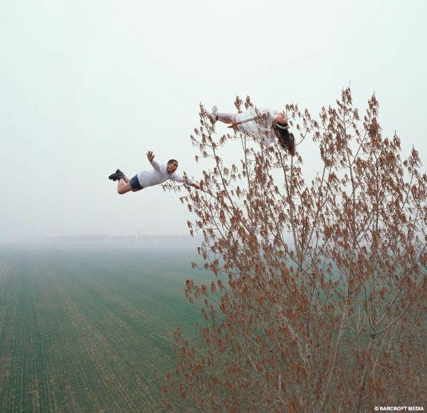 homem voando, salvando uma mulher em cima de uma árvore