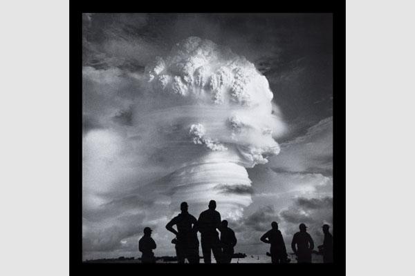 silhueta de pessoas assistindo explosão atomica