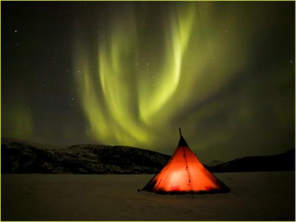 aurora boreal verde com tenda conica acesa de luz vermelha