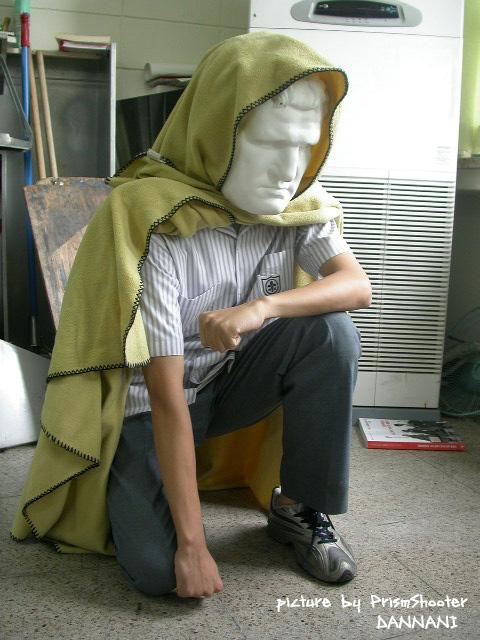 homem de capa verde com cabeca de estatua grega