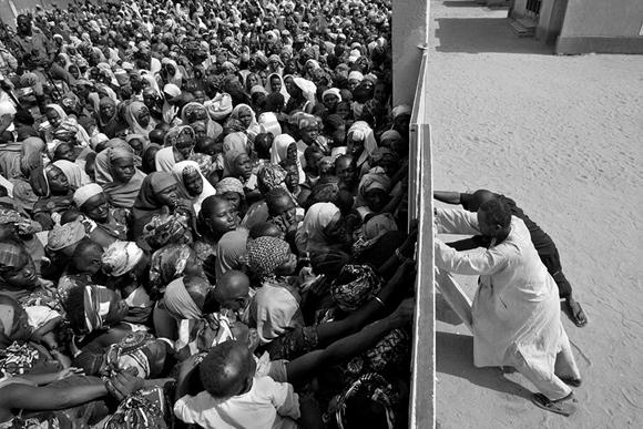 duas pessoas tentando conter multidão, visto de cima