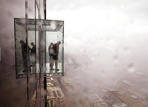 Vista lateral de um elevador de vidro grudado num prédio alto com gente dentro, nelbina em volta