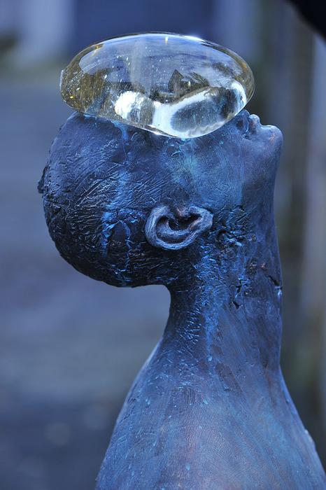 Escultura de homem azul com o rosto virado para cima e com uma bolha transparente equilibrada na cara