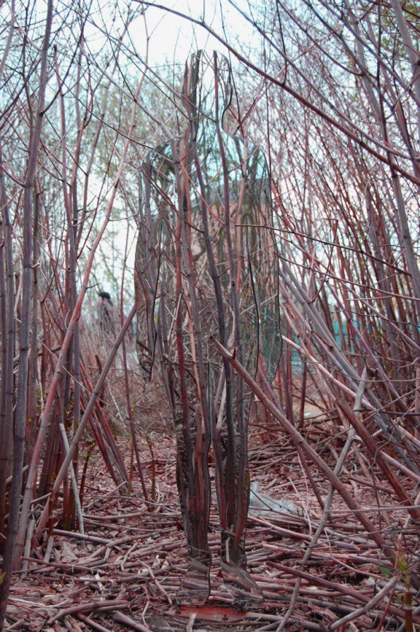 espelho recortado na forma de uma pessoa, instalado no meio de uma floresta