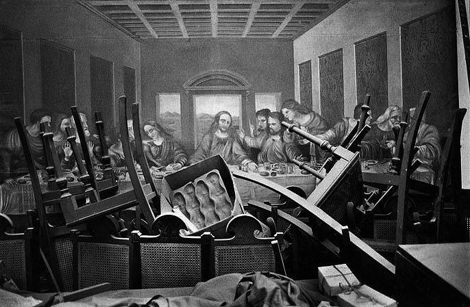 Foto de um quadro da Santa Ceia em uma parede com um monte de cadeiras empilhadas em frente a ele