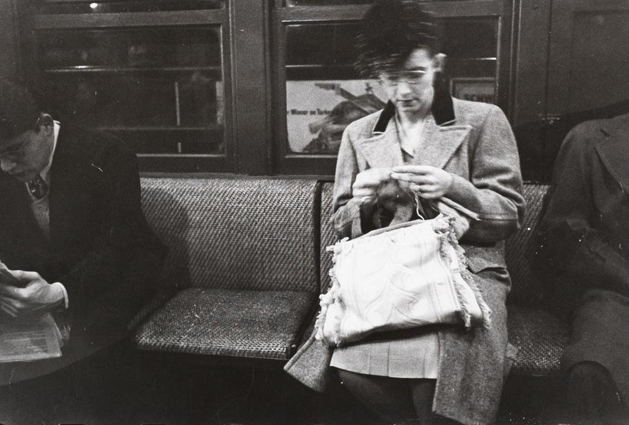foto preto e branco, tirada pelo Stanley Kubrick, de uma mulher sentada sozinha no trem, lendo algo