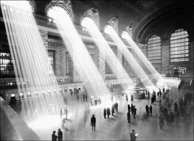 Plano bastante amplo do enorme saguão de uma estação de trem com pessoas circulando e raios de luz entrando pelas janelas superiores em direção às pessoas