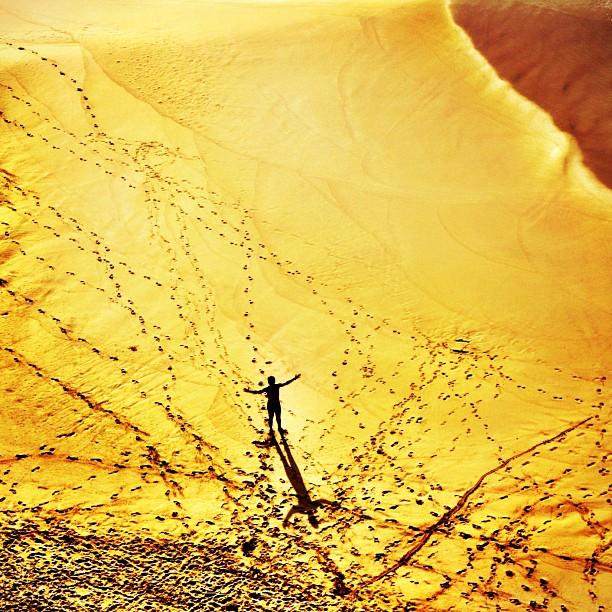 Dunas douradas vistas do alto com pessoinha de braços abertos projetando uma sombra na areia cheia de pegadas
