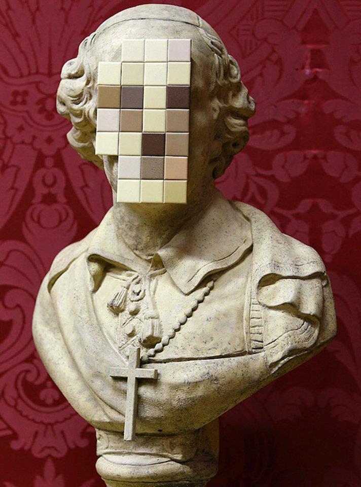 busto de um religioso feito em pedra mas com o rosto pixelado em quadradinhos de cor, como se fosse um arquivo digital