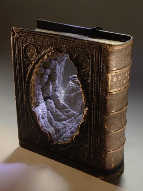 Livro de encadernação antiga com um buraco cavado no meio formando uma caverna