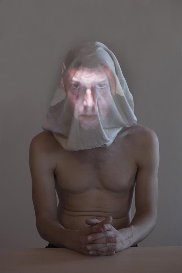 Homem de torso nu com tecido sobre a cabeça recebendo a projeção de um rosto