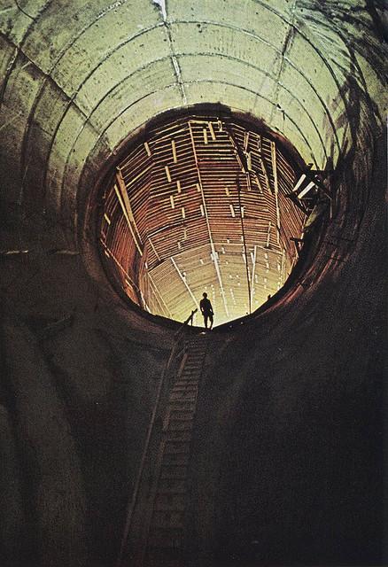 Entrada circula e imensa de estrutura arquitetônica de formato circular com uma pessoa pequena na entrada, subindo por uma escada