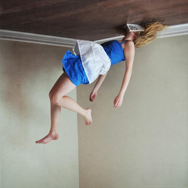 mulher jovem com roupa da Alice no Pais das Maravilhas flutuando com o rosto grudado em um livro aberto preso ao teto