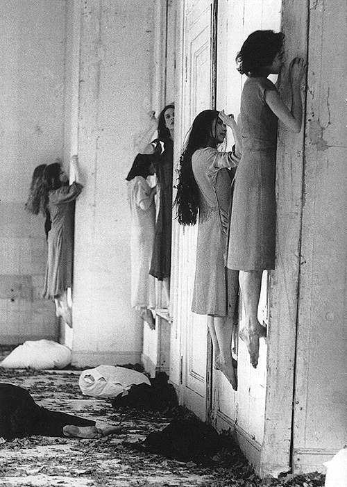 Foto preto e branco de várias mulheres grudadas na parede, como se estivessem levitando
