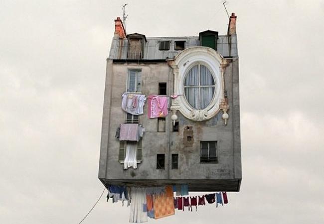 Casa voadora, com roupas no varal penduradas embaixo dela e várias janelas sendo uma delas uma janela oval