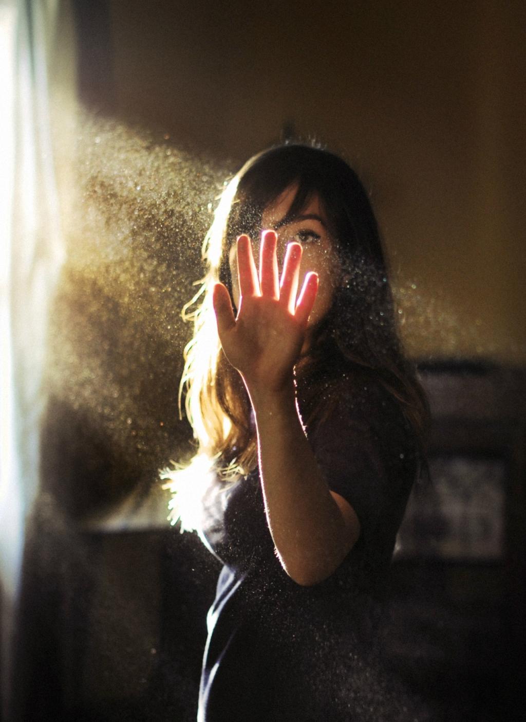 Mulher com a mão estendida para receber um raio de luz que entra pela janela