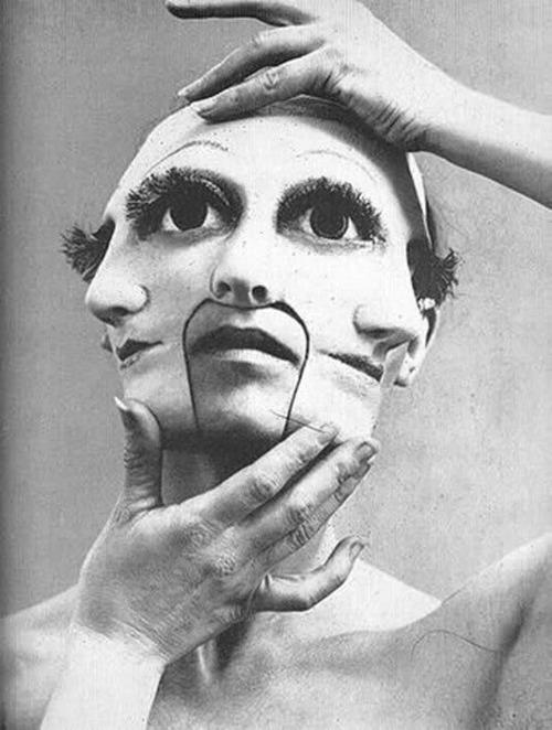 foto preto e branco de uma pessoa usando uma máscara com vários rostos de olhos grandes