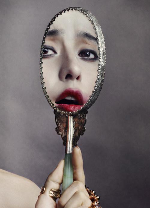 Mão feminina com anéis dourados segurando um espelho de mão em formato oval, refletindo apenas o rosto dela com batom vermelho e olhos maquiados olhando para você