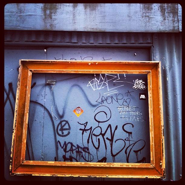 Moldura de quadro colocada sobre pichações, em uma parede na rua