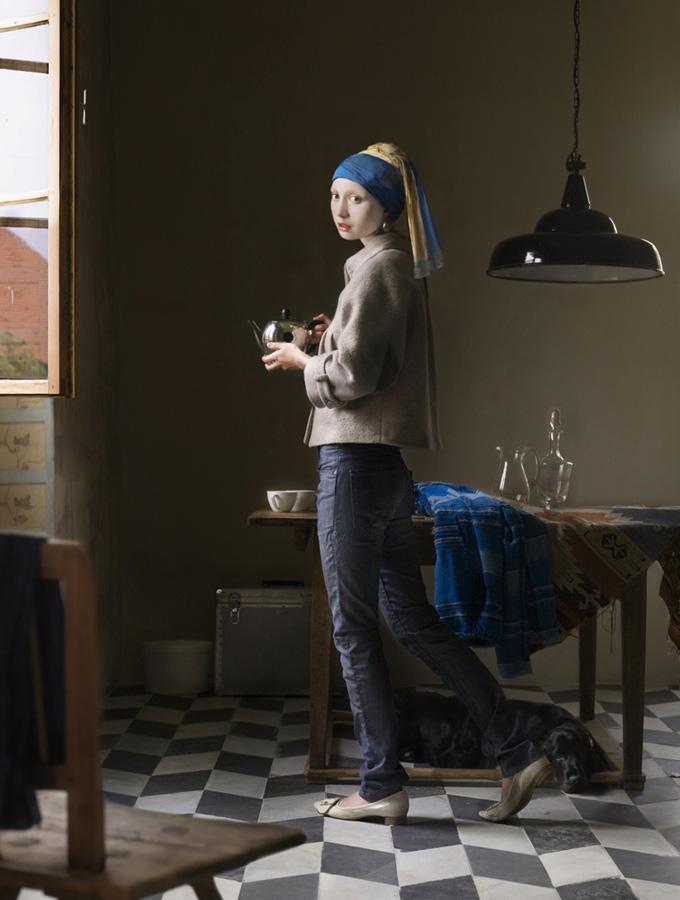Quadro famoso do Vermeer, moça com brinco de pérolas, onde a moça recebeu uma roupa moderna e está usando calça jeans e uma jaqueta e há um lustre moderno sobre a mesa