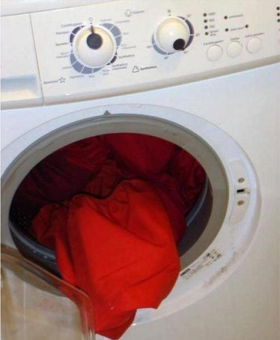 Foto colorida de uma maquina de lavar branca com a abertura circular formando uma boca com uma lingua de roupa vermelha saindo