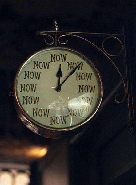 Relógio circular preso na parede de um local semi-aberto e  com a palavra NOW em todas as horas