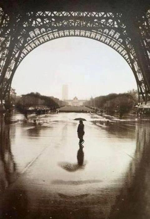 Foto PB de uma pessoa atravessando embaixo do vão da Torre Eiffell, tudo isso formando a imagem de um rosto