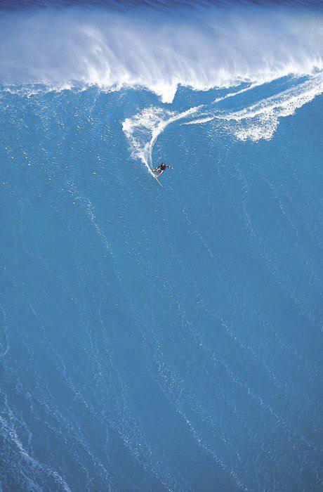 Um surfista descendo uma onda gigantesca e deixando um rastro nela