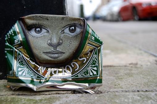 latinha amassada com um rosto desenhado na meia lua superior da peça