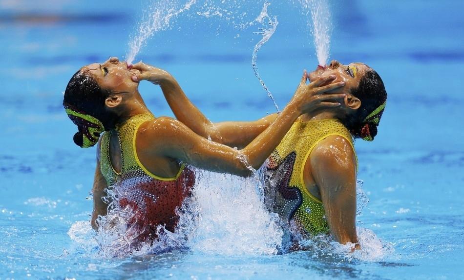 nadadoras de nado sincronizado de frente uma pra outra ambas cuspindo água como numa fonte