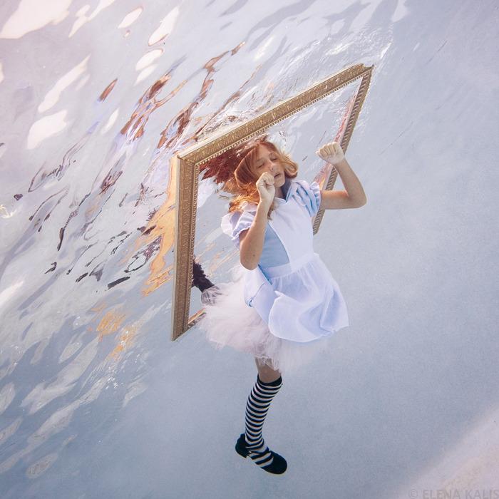 Menina vestida de Alice saindo de moldura de quadro vista debaixo dagua