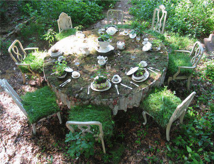 mesa de jantar com cadeiras e tralhres, tudo semi corberto por plantas e musgo