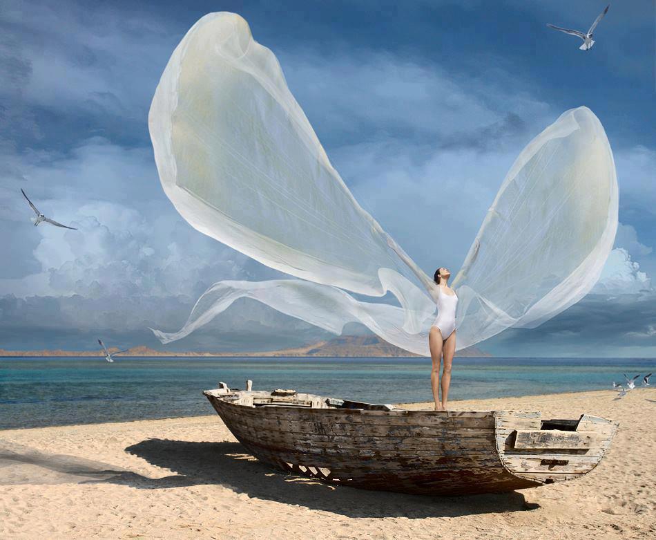 Mulher com vestido ao vento formando asas brancas, sobre bote em ruínas na areia branca de uma praia em dia de sol