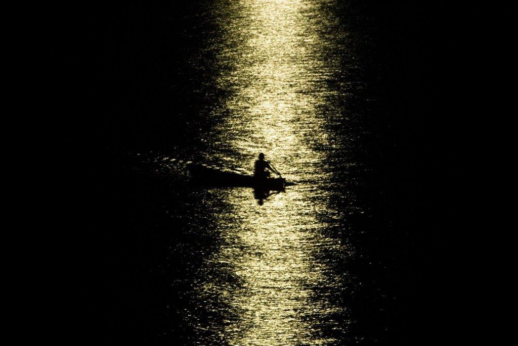 Foto de Anderson Barbosa mostrando a luz do luar (sem mostrar a lua) refletindo no mar formando um rio onde atravessa a silhueta de um bote com um homem
