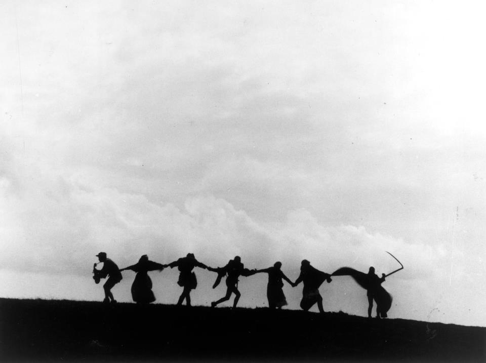 Frame do filme O Sétimo Selo do Bergman com a silhueta de 7 pessoas sendo levadas pela morte em uma colina com nuvens ao fundo