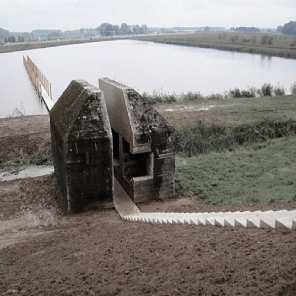 Bunker em formato de casa na beira de um lago, dividido pela metade por uma escada que o atravessa até entrar na água