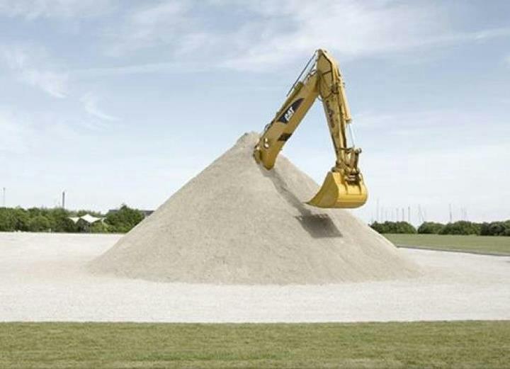 Um monte de areia com o braço mecânico de um trator escavadeira saindo de dentro do monte conico de areia