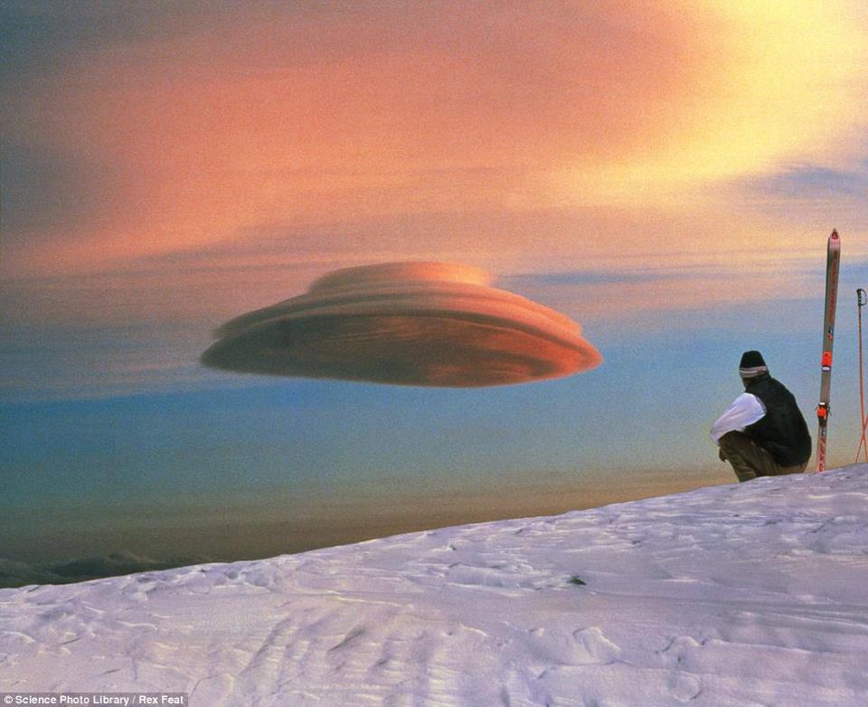 Esquiador sentado no alto, sobre uma areia branca e observando uma nuvem em forma de disco voador