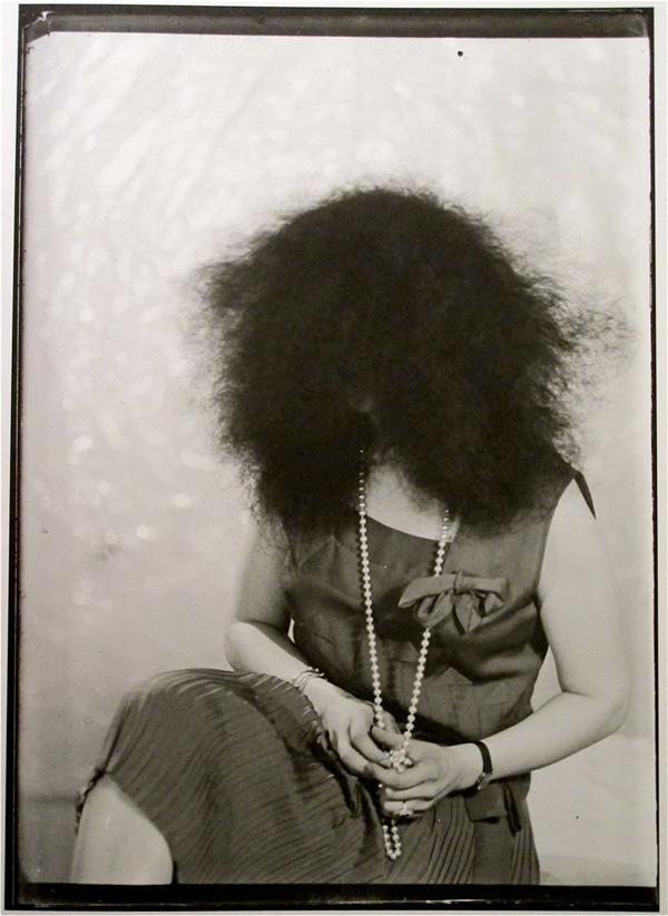Retrato antigo de uma mulher com vestido moderno sentada num cadeira com os cabelos desgrenhados cobrindo o rosto