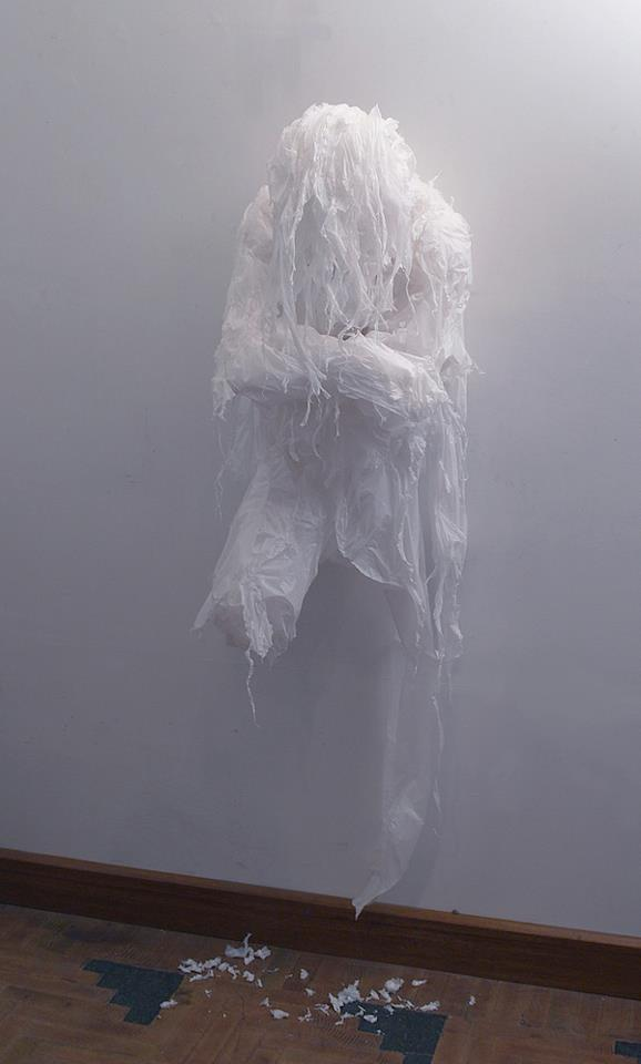 Escultura de cera grudada a  uma parede mostrando uma pessoa de braços cruzados mas sem a cabeça e as pernas