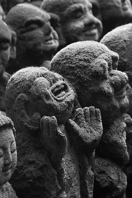 esculturas de monges budistas cabeçudos feitas de areia com expressões de rosto exageradas